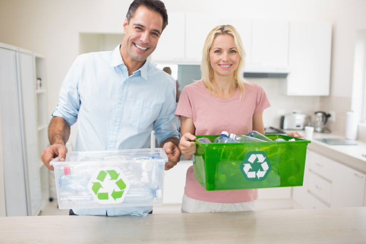 Portrait of a smiling couple carrying recycling containers in the kitchen at home
